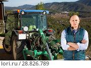 Купить «Confident male owner of vineyard posing near tractor outdoors in sunny day», фото № 28826789, снято 22 января 2018 г. (c) Яков Филимонов / Фотобанк Лори