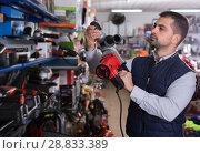 Man choosing drilling machine. Стоковое фото, фотограф Яков Филимонов / Фотобанк Лори