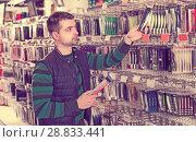 Купить «Young man consumer choosing ocean fishing lures in shop», фото № 28833441, снято 16 января 2018 г. (c) Яков Филимонов / Фотобанк Лори