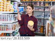 Купить «Woman is choosing with paint for repair», фото № 28833509, снято 16 февраля 2018 г. (c) Яков Филимонов / Фотобанк Лори