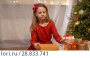 Купить «happy girl opening christmas gift at home», видеоролик № 28833741, снято 26 июля 2018 г. (c) Syda Productions / Фотобанк Лори