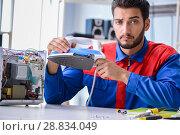 Купить «Man repairman repairing iron at service center», фото № 28834049, снято 11 июля 2017 г. (c) Elnur / Фотобанк Лори