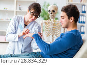Купить «Doctor showing type of injury on skeleton to patient», фото № 28834329, снято 28 февраля 2018 г. (c) Elnur / Фотобанк Лори
