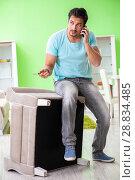 Купить «Man repairing furniture at home», фото № 28834485, снято 14 мая 2018 г. (c) Elnur / Фотобанк Лори
