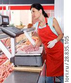 Купить «Female seller weighing sausages in shop», фото № 28835105, снято 22 июня 2018 г. (c) Яков Филимонов / Фотобанк Лори