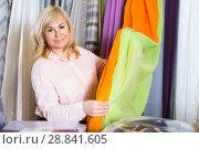Купить «Mature woman customer choosing color curtains», фото № 28841605, снято 17 января 2018 г. (c) Яков Филимонов / Фотобанк Лори