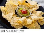 Купить «Nachos chips with sauces on black plate», фото № 28841749, снято 22 апреля 2019 г. (c) Яков Филимонов / Фотобанк Лори