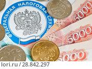 Купить «Деньги (монеты и купюры) лежат на письме из налоговой. Эмблема федеральной налоговой службы крупным планом», фото № 28842297, снято 28 июля 2018 г. (c) E. O. / Фотобанк Лори