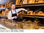 Купить «Assistant baker offers a variety of delicious bread», фото № 28842545, снято 26 января 2017 г. (c) Яков Филимонов / Фотобанк Лори