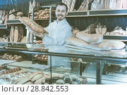 Купить «Man baker showing warm tasty bun in bakery», фото № 28842553, снято 26 января 2017 г. (c) Яков Филимонов / Фотобанк Лори