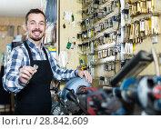 Купить «male worker showing key he made in repair workshop», фото № 28842609, снято 2 февраля 2017 г. (c) Яков Филимонов / Фотобанк Лори