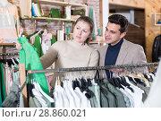 Купить «Young female with male are looking on green jacket for her», фото № 28860021, снято 12 марта 2018 г. (c) Яков Филимонов / Фотобанк Лори