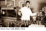 Купить «Adult male holding newly produced bottle of wine», фото № 28860153, снято 21 сентября 2016 г. (c) Яков Филимонов / Фотобанк Лори