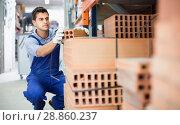 Купить «Sellerman is calculating bricks before selling», фото № 28860237, снято 26 июля 2017 г. (c) Яков Филимонов / Фотобанк Лори