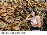 Купить «Симпатичная женщина стоит возле стопки сложенных дров», эксклюзивное фото № 28860465, снято 5 июня 2018 г. (c) Игорь Низов / Фотобанк Лори