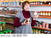 Купить «Woman customer choosing tin canned goods in store», фото № 28868781, снято 15 декабря 2017 г. (c) Яков Филимонов / Фотобанк Лори