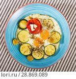 Купить «Image of plate with fried eggs with tomatoes and zucchini», фото № 28869089, снято 17 августа 2018 г. (c) Яков Филимонов / Фотобанк Лори
