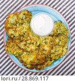 Купить «Top view of zucchini pancakes with sour cream», фото № 28869117, снято 15 октября 2018 г. (c) Яков Филимонов / Фотобанк Лори