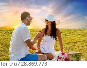 Купить «smiling couple with small red gift box at picnic», фото № 28869773, снято 23 июля 2014 г. (c) Syda Productions / Фотобанк Лори