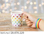 Купить «hand with cup of cacao and gay awareness wristband», фото № 28870229, снято 14 ноября 2017 г. (c) Syda Productions / Фотобанк Лори