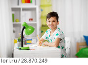 Купить «happy little boy writing to notebook at home», фото № 28870249, снято 19 апреля 2018 г. (c) Syda Productions / Фотобанк Лори