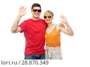 Купить «couple in sunglasses hugging and waving hands», фото № 28870349, снято 30 июня 2018 г. (c) Syda Productions / Фотобанк Лори