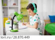 Купить «boy in headphones with textbook learning at home», фото № 28870449, снято 19 апреля 2018 г. (c) Syda Productions / Фотобанк Лори
