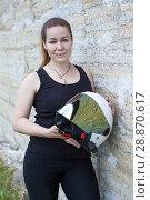Купить «Девушка с мотоциклетным шлемом стоит возле каменной стены», фото № 28870617, снято 16 июня 2018 г. (c) Кекяляйнен Андрей / Фотобанк Лори