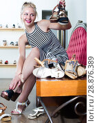Купить «girl trying on pair of sandals in shoe store», фото № 28876389, снято 23 сентября 2018 г. (c) Яков Филимонов / Фотобанк Лори