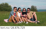 Купить «smiling friends with tablet pc sitting on grass», видеоролик № 28876729, снято 19 июля 2018 г. (c) Syda Productions / Фотобанк Лори