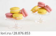 Купить «yellow and pink macarons on glass stands», видеоролик № 28876853, снято 13 июля 2018 г. (c) Syda Productions / Фотобанк Лори