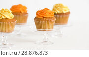 Купить «cupcakes with frosting on confectionery stands», видеоролик № 28876873, снято 13 июля 2018 г. (c) Syda Productions / Фотобанк Лори