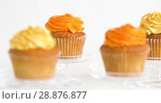 Купить «cupcakes with frosting on confectionery stands», видеоролик № 28876877, снято 13 июля 2018 г. (c) Syda Productions / Фотобанк Лори
