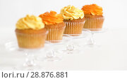Купить «cupcakes with frosting on confectionery stands», видеоролик № 28876881, снято 13 июля 2018 г. (c) Syda Productions / Фотобанк Лори