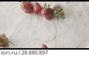 Купить «Close-up drops of milk and a bunch of ripe red strawberry fruit, one, then several, falls into a white plate with milk splashes. Top view. Slow motion. Soft focus. Full HD video, 240fps,1080p.», видеоролик № 28880897, снято 29 июня 2018 г. (c) Ярослав Данильченко / Фотобанк Лори