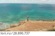 Купить «Woman at the edge of the cliff watching seascape», видеоролик № 28890737, снято 16 июля 2018 г. (c) Илья Шаматура / Фотобанк Лори