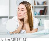 Купить «Smiling female is looking on her skin in the mirror», фото № 28891721, снято 29 марта 2018 г. (c) Яков Филимонов / Фотобанк Лори