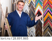 Купить «portrait of man in uniform choosing framing moulding in studio», фото № 28891865, снято 19 января 2019 г. (c) Яков Филимонов / Фотобанк Лори