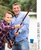 Купить «Happy parent and boy fishing together on freshwater lake», фото № 28891901, снято 17 августа 2018 г. (c) Яков Филимонов / Фотобанк Лори