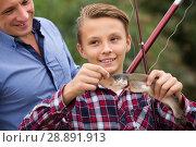 Купить «Happy man with son looking at fish on hook», фото № 28891913, снято 10 декабря 2018 г. (c) Яков Филимонов / Фотобанк Лори
