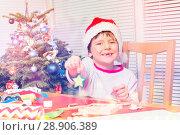 Купить «Cheerful boy preparing own Christmas ornaments», фото № 28906389, снято 31 декабря 2016 г. (c) Сергей Новиков / Фотобанк Лори