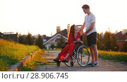 Купить «Girl In A Wheelchair Cute Talking To Her Young Man On The Background Of The House, Green Grass And Trees», видеоролик № 28906745, снято 26 сентября 2018 г. (c) Константин Шишкин / Фотобанк Лори