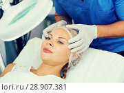 Купить «Specialist is analysing skin of female patient with using magnification before the procedure», фото № 28907381, снято 7 августа 2017 г. (c) Яков Филимонов / Фотобанк Лори