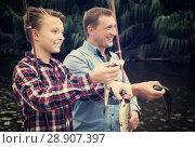 Купить «Man with teenager boy showing catch fish», фото № 28907397, снято 17 сентября 2016 г. (c) Яков Филимонов / Фотобанк Лори