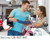 Купить «Couple discussing the purchase of a motorcycle», фото № 28907441, снято 8 мая 2018 г. (c) Яков Филимонов / Фотобанк Лори