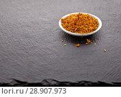 Купить «Dried crushed spices for fish in a white saucer on a black slate background», фото № 28907973, снято 8 августа 2018 г. (c) Элина Гаревская / Фотобанк Лори