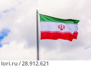 Купить «The national flag of Iran flutters in the wind against the blue cloudy sky.», фото № 28912621, снято 21 июня 2018 г. (c) Акиньшин Владимир / Фотобанк Лори