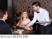 Купить «Polite waiter bringing ordered dishes to smiling couple at restaurant», фото № 28913549, снято 8 января 2018 г. (c) Яков Филимонов / Фотобанк Лори