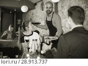 Купить «waiter bringing ordered dishes to smiling couple», фото № 28913737, снято 18 декабря 2017 г. (c) Яков Филимонов / Фотобанк Лори