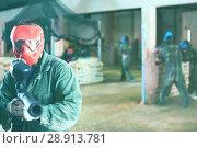 Купить «Portrait of red team player who is aiming in opponents on paintball field.», фото № 28913781, снято 10 июля 2017 г. (c) Яков Филимонов / Фотобанк Лори